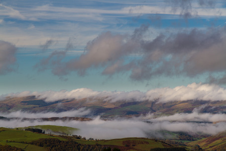 inversion: Welsh countryside with cloud clinging to hills in temperature inversion. Powys, Wales, United Kingdom.