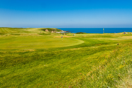 MORFA NEFYN – JUNE 3: Golf course putting green with golfers, sea in background, June 3, 2016 in Morfa Nefyn.