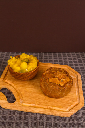 Piccalilli relish in a wooden bowl on a board. Stock Photo