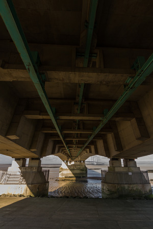 ail: Beneath the Second Severn crossing is a bridge that carries the M4 motorway over the Bristol Channel or River Severn Estuary between England and Wales, United Kingdom. Morning light from the east. Stock Photo