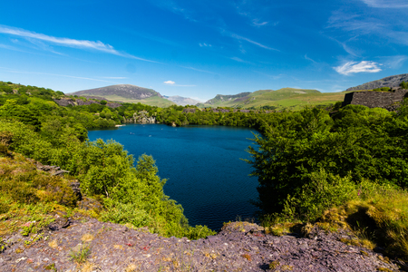 Looking across the disused Dorothea Slate Quarry to Snowdon, Nantlle, Gwynedd, Wales, United Kingdom. Flooded with water.