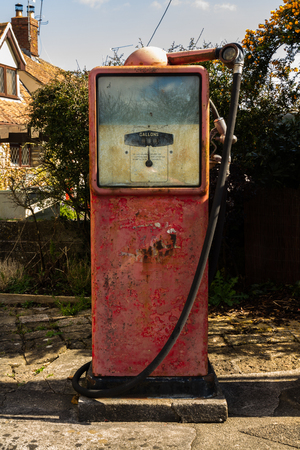 fuelling pump: Old red derelict petrol pump, no logo.
