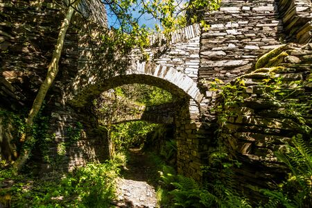 Two stone flying buttresses keeping slate stacks upright. Dorothea Slate Quarry, Nantlle, Gwynedd, Wales, United Kingdom. Stock Photo