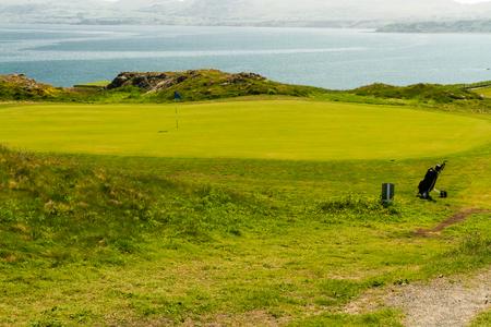 Clifftop putting green with bag and sea, Nefyn & District Golf Club, Morfa Nefyn, Llyn Peninsula, Gwynedd, Wales, United Kingdom Stock Photo