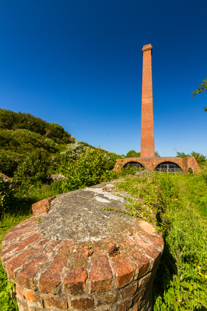 tall chimney: Old brick ruins with tall chimney and  blue sky. Cemaes Brickworks, Anglesey, Wales, United Kingdom, Europe Stock Photo