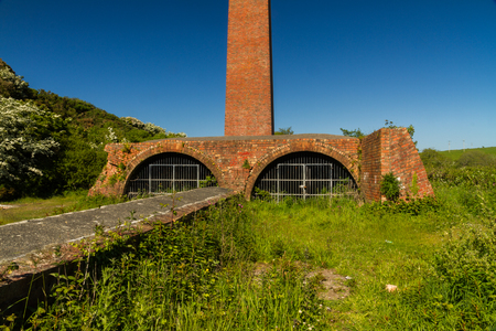 Old brick ruins with tall chimney and  blue sky. Cemaes Brickworks, Anglesey, Wales, United Kingdom, Europe Stock Photo