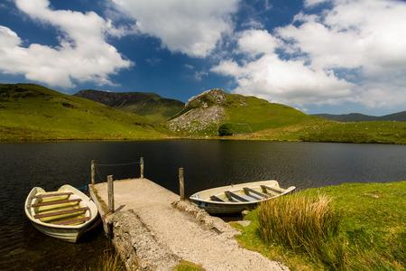 Two boats moored to Jetty by small lake. Llyn y Dywarchen Reservoir, Rhyd Ddu, Gwynedd, Wales, United Kingdom