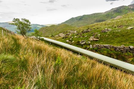 Water pipe from lake Llyn Llydaw on Snowdon to Cwm Dyli hydroelectric power station. Snowdonia, Wales, United Kingdom.