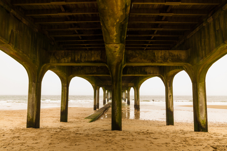 View to sea below concrete pier on sandy beach. Boscombe Pier, Bournemouth, Dorset, England, United Kingdom.