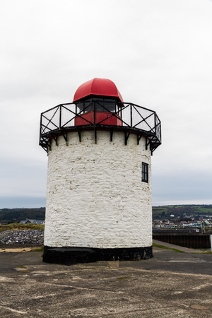 Small white squat white lighthouse with red top. Burry Port, Llanelli, Carmarthenshire, Wales. Stock Photo