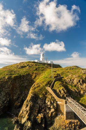 Stumble head lighthouse on a sunny day with bridge and steps. Pencaer, Pembrokeshire, Wales, United Kingdom. Stock Photo