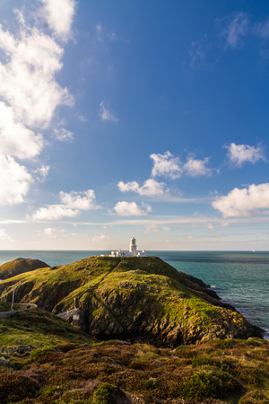 Stumble head and lighthouse on a sunny day. Pencaer, Pembrokeshire, Wales, United Kingdom.
