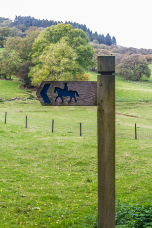 Wooden sign with picture of horse and rider to indicate public bridleway, United Kingdom