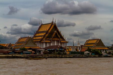 Wat Kalayanamitr Varamahavihara Buddhist Temple with boat in front. Chao Phraya River, Bangkok, Thailand.