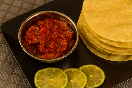 Indian poppadums stacked with bowl of lime pickle and sliced lime