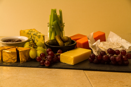 Cheeseboard, platter for sharing, cheese, red Leicester, stilton, cheddar, camembert, brie, grapes, pickled gherkins, celery, pickle or chutney on slate.