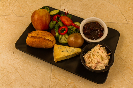 Ploughman's lunch with stilton cheese, pickle, pickled onion, salad, coleslaw and bread roll and apple.