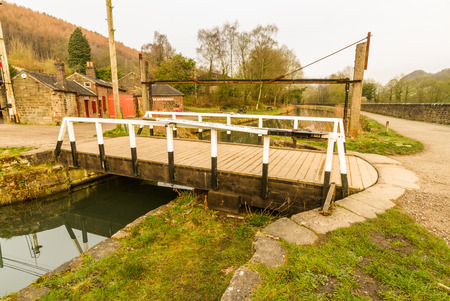 Small swing bridge over the Cromford Canal, Canal, Peak District, Derbyshire, England, UK. Editorial