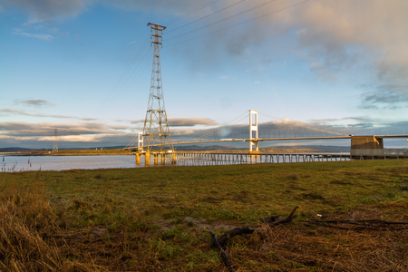 The old Severn Crossing (welsh Pont Hafren) bridge that crosses from England to Wales across the rivers Severn and Wye. Morning light, pylon in foreground.