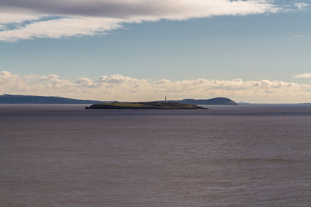 Flat Holm island with lighthouse in Bristol Channel. From Wales, Somerset and Avon Coast of England in the distance, United Kingdom. Stock Photo