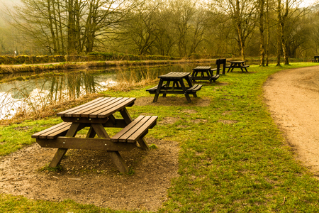 Picnic tables lined along bank of canal, United Kingdom. Stock Photo