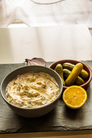 Home made tartar sauce in grey bowl with gherkins, lemon and onion. Stock Photo