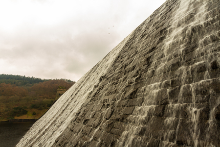 Water cascades down the Derwent Dam, Ladybower reservoir. Near Sheffield, in Peak District, Derbyshire, England, United Kingdom.