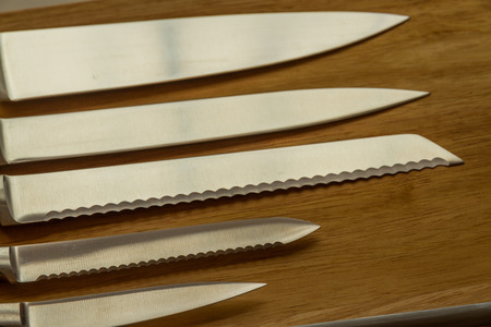 Cook's knives in line on chopping board.