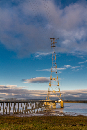 High electrical pylon next to the Severn Crossing, Aust, United Kingdom. Morning light. Stock Photo