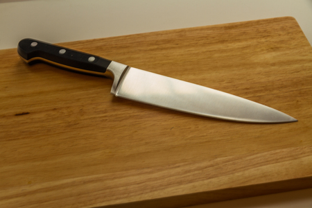 Quality cook or chef knife on wood chopping board