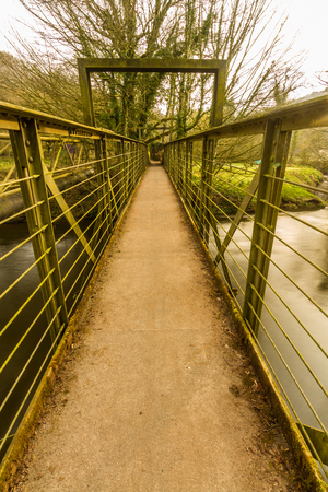 Narrow footbridge over river in early morning light.