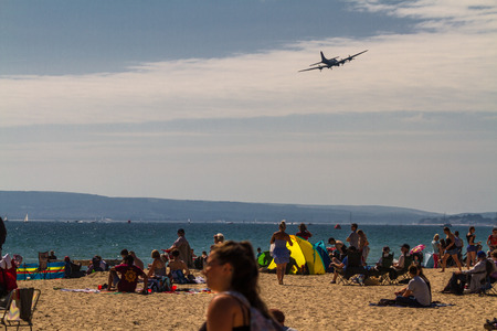 Bournemouth, United Kingdom – Bournemouth Air Festival 2018 spectators on beach Sally-B B17 Flying Fortress aeroplane on September 2 2018 in Bournemouth. Editorial
