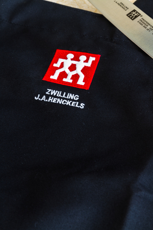 Illustrative editorial of Zwilling J.A. Henckels kitchen knife and black apron with logo, copyspace – Bournemouth, United Kingdom – June 15th, 2018