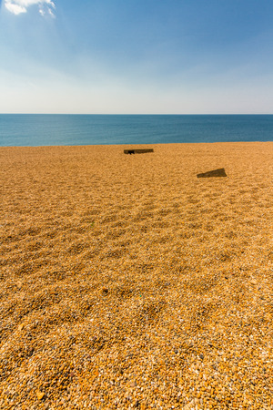 Background, gravel foreground, with, sea,  blue sky and cloud. The Chesil Beach, Dorset, England, UK.