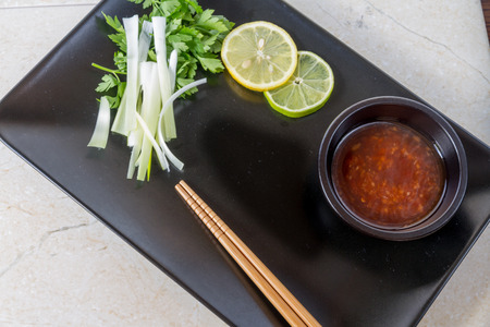 Black hexagon plate with copyspace for oriental food, chop sticks, lime, lemon, spring onions, scallions and sweet chilli dipping sauce.