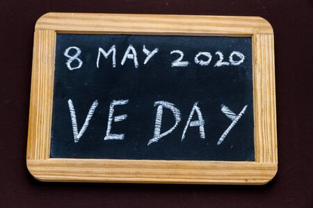 UK may bank holiday moved from 4 to 8 May 2020 to celebrate 75 years of end of WWII VE Day on old fashioned school writing slate.