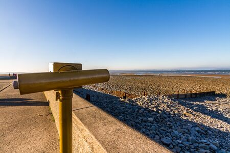 Llanfairfechan beach and coin operated telescope on November day, Conwy, North Wales.