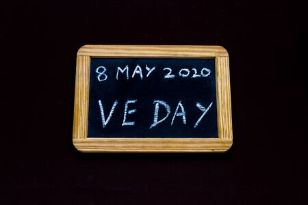 UK may bank holiday moved from 4 to 8 May 2020 to celebrate 75 years of end of WWII VE Day on old fashioned school writing slate, copyspace Imagens