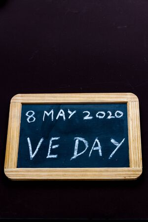 UK may bank holiday moved from 4 to 8 May 2020 to celebrate 75 years of end of WWII VE Day on old fashioned school writing slate, copyspace, portrait Imagens