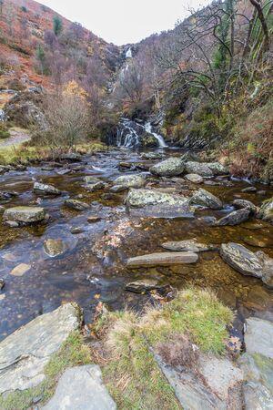 River Eiddew with Rhiwargor waterfall in the distance. Lake Vyrynwy, Powys, Wales UK, portrait Imagens