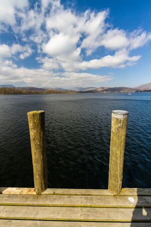 Mooring posts with lake Windermere and mountains behind, portrait.