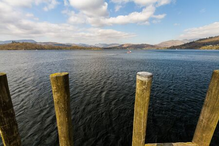 Mooring posts with lake Windermere and mountains behind, landscape, wide angle.