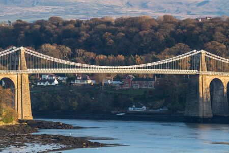 Historical Menai Bridge, welsh Pont Grog y Borth suspension bridge over the menai straits, landscape, trees in background