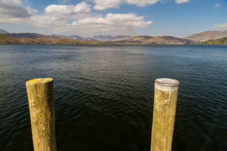 Mooring posts with lake Windermere and mountains behind, landscape.