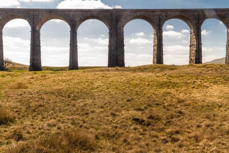 Arches against blue sky and cloud of the Ribblehead Viaduct, landscape. North Yorkshire, Europe, England, landscape and telephoto. Фото со стока