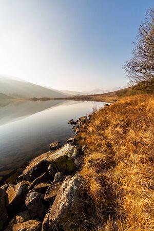 Morning autumn fall view of misty lake. Llynnau Mymbyr, Capel Curig, Snowdonia national Park, Gwynedd, Wales, UK, portrait, wide angle.