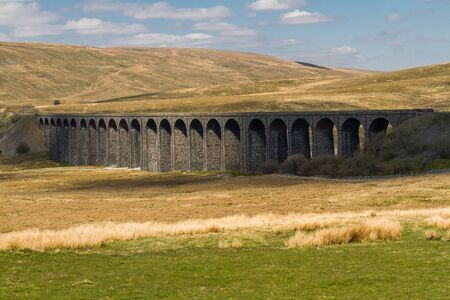 Ribblehead Viaduct, landscape with hills behind, telephoto. Фото со стока