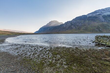 Morning light on snow capped peak of Tryfan from banks of Lake or Llyn Idwal. Snowdonia national Park, Gwynedd, Wales, UK. Landscape, wide angle. Stock fotó
