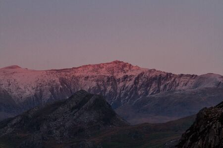 Last sun of the day on snow covered Snowdon Mountain. Landscape Фото со стока