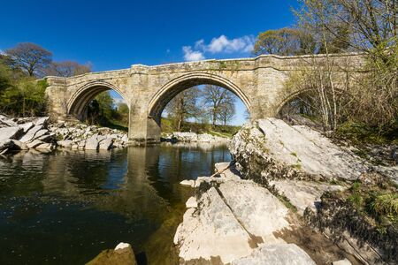 Looking up at Devils Bridge, over the River Lune. Kirkby Lonsdale, Cumbria, England, landscape, wide angle. Фото со стока